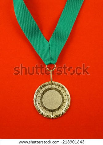 Gold medal with green ribbon on red velveteen