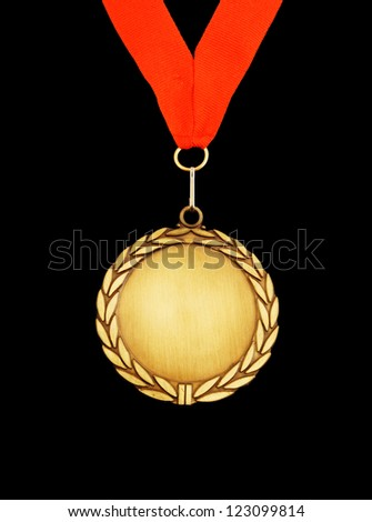 Gold medal with red ribbon isolated on black - stock photo
