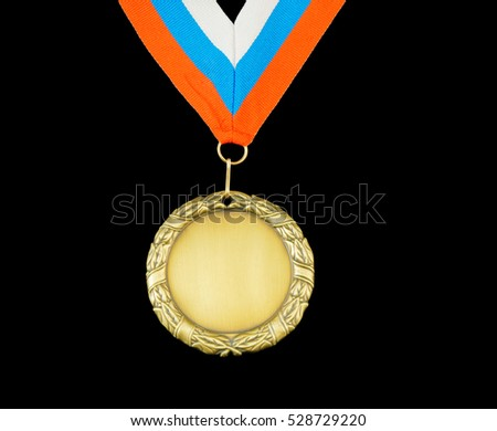 Gold medal with ribbon isolated on black.