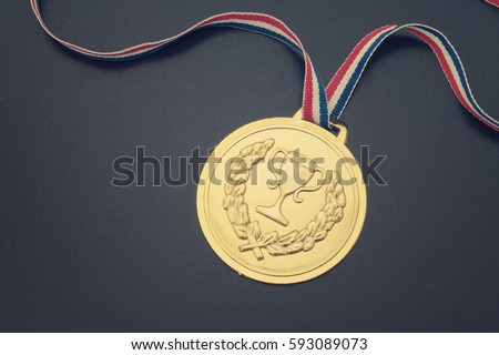 stock-photo-gold-medal-with-ribbon-on-bl