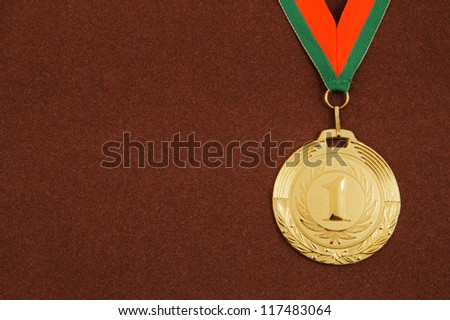 Gold medal with ribbon on brown velveteen