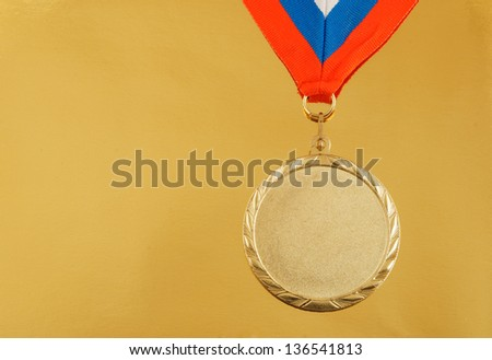 Gold medal with ribbon on golden background