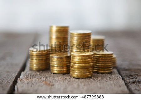 Gold money coins pile on wooden table