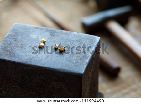 Gold nuggets on a old anvil, with tools in background. - stock photo