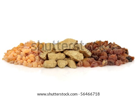 Gold nuggets, with frankincense and myrrh resin either side , isolated over white background.
