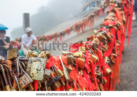 Gold padlocks and red ribbons at Gold Lock pass on Mount Hua, near Huayin in Shaanxi province. One of the Five Great Mountains of China, and has a long history of religious significance. - stock photo