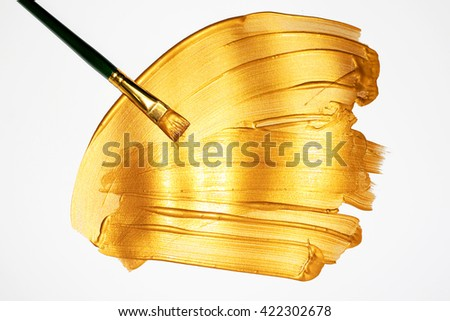 Gold paint brush stroke and brush - stock photo