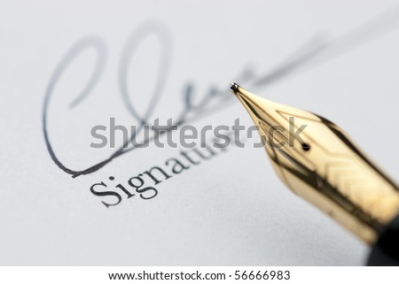Gold pen with signature and document in background. Focus on tip of fountain pen nib. - stock photo