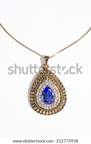 gold pendant with blue gem on a white background - stock photo