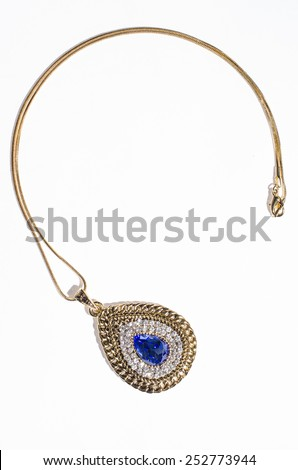 gold pendant with  blue stones on a white background - stock photo
