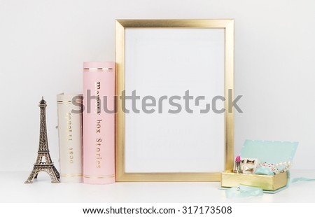 gold picture frame with decorations. Mock up for your photo or text Place your work, print art,shabby style, white background,, pastel color book, paris, lipstick, mint and gold accessories  - stock photo