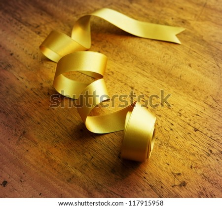 Gold ribbon nicely uncurled, on old wooden desk. - stock photo
