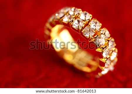 Gold ring on red textured background. - stock photo