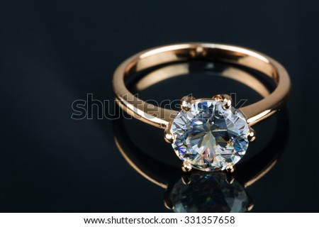 Gold ring with brilliant isolated on black background - stock photo