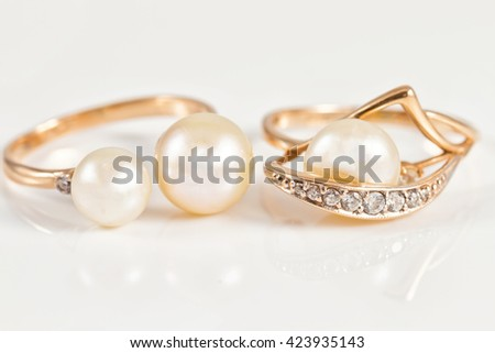 gold rings with pearls on a white reflective surface