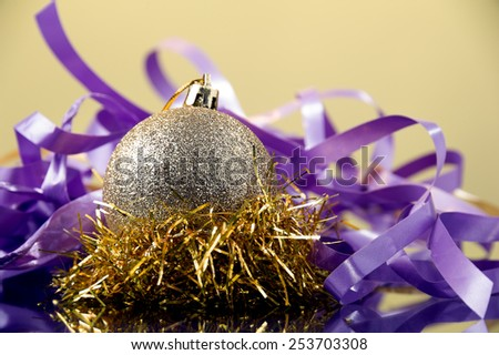 gold round Christmas decoration with diffuse surface placed on gold and violet ribbon against yellow background   - stock photo
