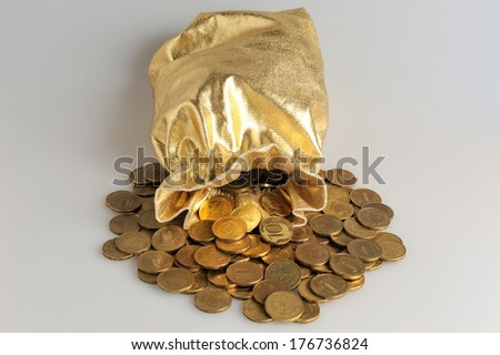 Gold sack with scattered coins on gray background - stock photo