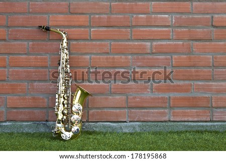 Gold saxophone on green grass floor lean against brick wall background, a blowing musical instrument. - stock photo