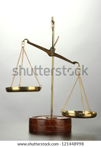 Gold scales of justice on grey background - stock photo