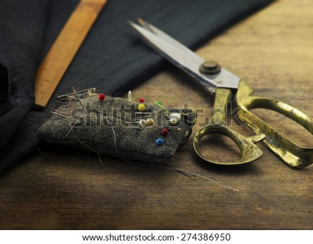 Gold scissors pin cushion, and black fabric.Measuring, cutting, sewing textile or fine cloth. Work table of a tailor. Shallow depth of field, Focus in on  pin on the pin cushion. - stock photo