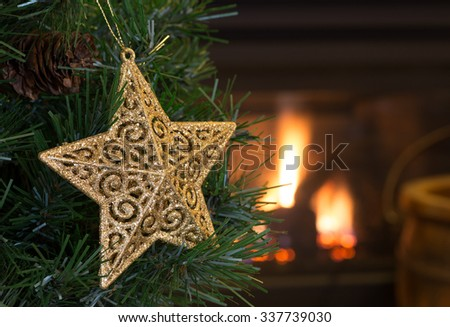 Gold star hanging on a Christmas tree with a fireplace in background
