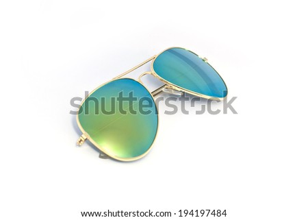 Gold sun glasses have a lens glass green yellow reflecting on an isolated white background  - stock photo