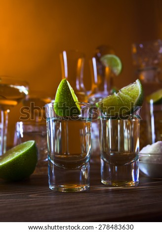 gold tequila , lime and salt on wooden table