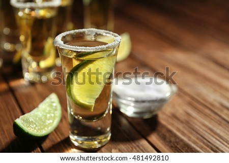 Gold tequila shot with lime on wooden background