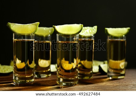 Gold tequila shots with lime on wooden table