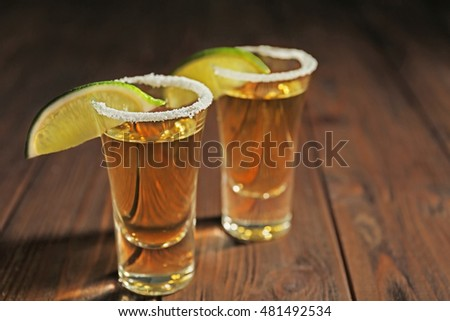 Gold tequila shots with lime slices and salt on wooden background