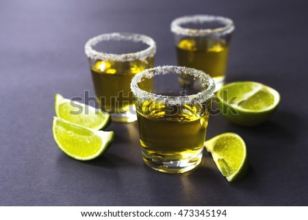 Gold tequila with lime and salt on dark table. Selective focus