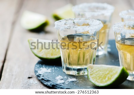 Gold tequila with lime and salt, selective focus