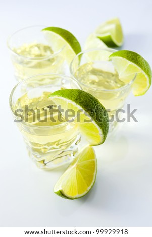 gold tequila with lime on a white reflective background. - stock photo