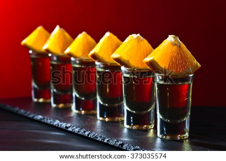 Gold tequila with orange on a red background - stock photo