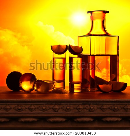 gold tequila with salt and lime on old table - stock photo