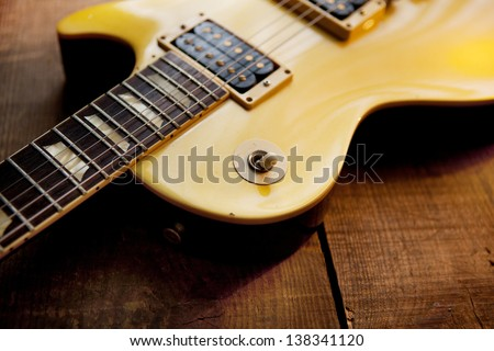 Gold top guitar on rough wood surface. - stock photo