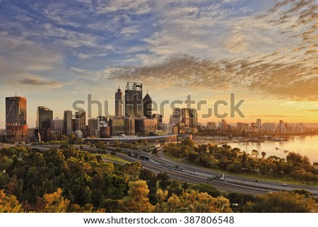 Gold warm sun light lightens he CBD of Perth city as seen from Kings park with green trees and highway entering the city.