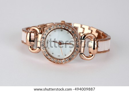 Gold watch with rhinestones . on a gray background .