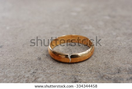 Gold wedding ring with a crack in it -- divorce concept                                - stock photo