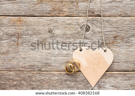Gold wedding rings and paper heart nanging on wooden background - stock photo