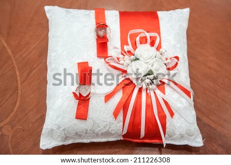 Gold wedding rings lie on a beautiful holiday pillow. - stock photo