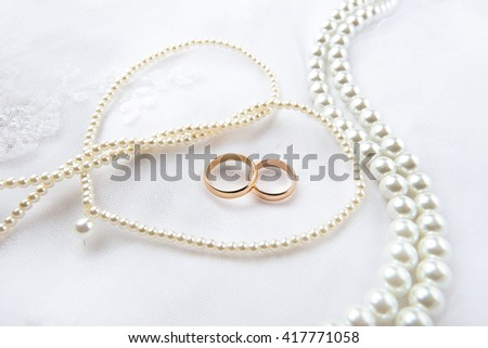 Gold wedding rings lie on a wedding dress. Against the background of the necklace of pearls  - stock photo