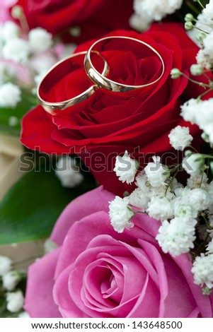 Gold wedding rings on a bunch of flowers for the bride - stock photo