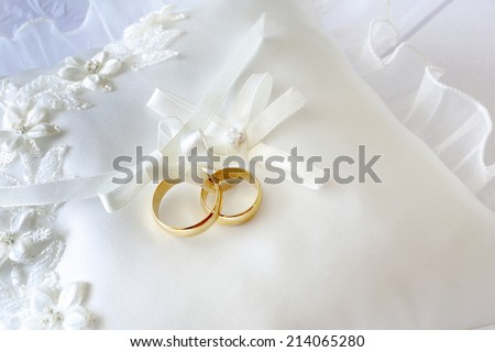 Gold wedding rings on a pillow with ribbons - stock photo