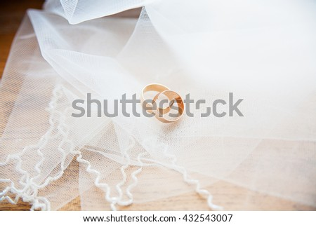 Gold wedding rings on a white veil