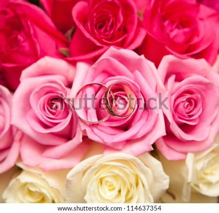 Gold wedding rings on flower - stock photo