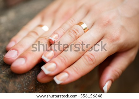 Gold wedding rings on the hands of the newlyweds
