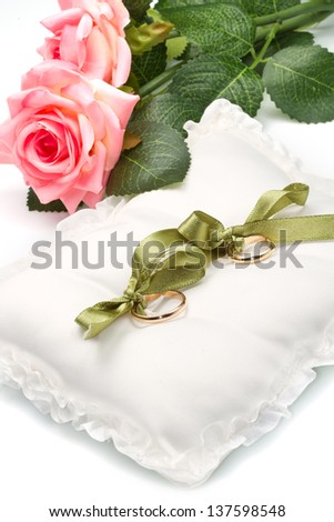 gold wedding rings on white pillow with rose - stock photo