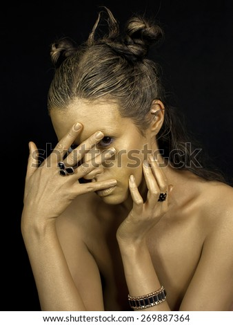 gold young woman face with ring, bijou on black background. Fashion style