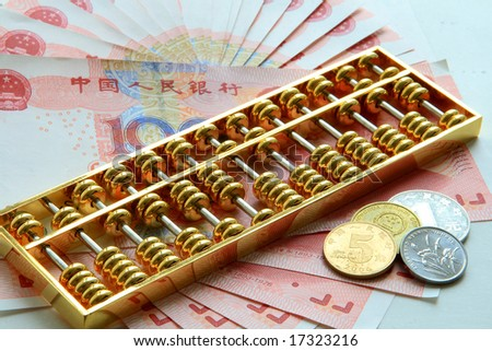 golden abacus with chinese bank notes and coins as background - stock photo